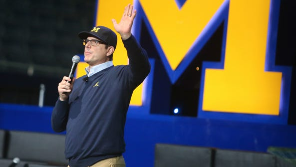 Michigan head coach Jim Harbaugh talks with fans during