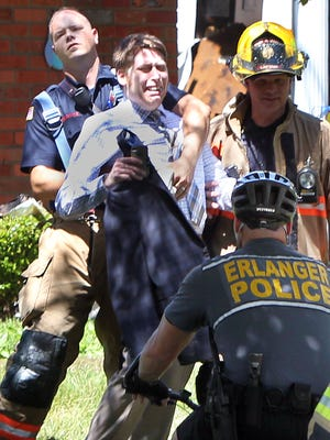 A firefighter restrains a man who attempted to run into one of the apartments heavily damaged by fire in the 3200 block of Talbot Avenue, Erlanger. Neighbors said he was likely concerned about a cat in his apartment.  Ernie Jones, a roofer who was working on the roof of the apartment when the fire broke out,  said he and his co-workers opened all the doors on the building so pets could escape.