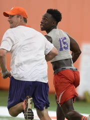 Receiver Derion Kendrick runs a rout with Clemson co-offensive coordinator Jeff Scott during Dabo Swinney's football camp Tuesday, June 9, 2015.