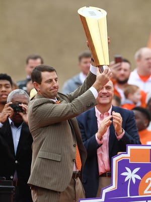 Clemson head coach Dabo Swinney holds the CFP National Championship Trophy during Clemson's National Championship celebration in Memorial Stadium on Saturday, January 14, 2017.