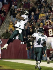 FILE - In this Dec.16, 2001, file photo, Philadelphia Eagles' Brian Dawkins, left, intercepts a pass in the end zone in front of Washington Redskins' Zeron Flemister (89) and Eagles' Famon Moore (43) during the fourth quarter of an NFL football game in Landover, Md. Dawkins will be inducted into the Hall of Fame during ceremonies in Canton, Ohio on Saturday, Aug. 4, 2018. (AP Photo/Stephen J. Boitano, File)