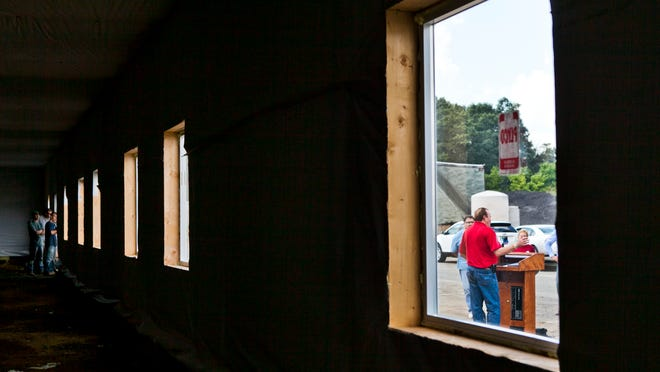 Gloucester County freeholder director Robert Damminger is seen through a window of a discount spay/neuter clinic that is under construction at Gloucester County Animal Shelter as workers, left, listen to him speak during a press conference, Friday, September 5, 2014 in Clayton. The 4,000 square foot building will house everything for the county-built, but independently operated low-cost clinic for those who adopt pets from places other than the county shelter.