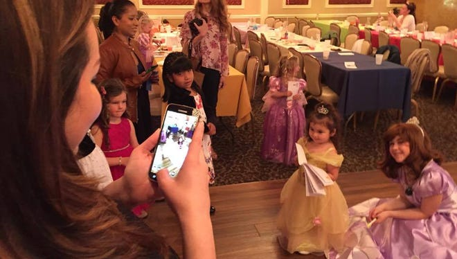 """Olivia Pineiro, 2, poses with an actor playing Sofia from the TV series """"Sofia the First"""" as her mother, Joan Pineiro, 34, takes a photo. She was dressed as Belle from """"Beauty and the Beast."""""""