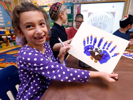 Second-grader Rozie Aronov, 7, holds up a menurkey, a paper-and-paint mashup of a menorah and turkey she created at Hillel Day School in Farmington Hills, Mich., Wednesday, Nov. 20, 2013. The recent class project reflects one way for Jews in the United States to deal with a rare quirk of the calendar that overlaps Thanksgiving with the start of Hanukkah. The last time it happened was 1888 and the next time is 79,043 years from now _ by one estimate that?s widely repeated in Jewish circles.