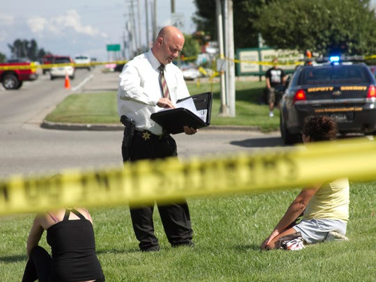 A Livingston County Sheriff Department Detective Lt. Domine speaks with possible witnesses to the shooting death of a subject near the intersection of Grand River Avenue and Chilson Roads in Genoa Twp.