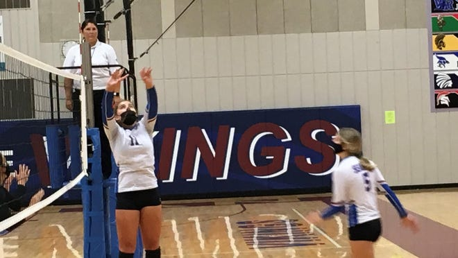 Seaman junior Drew Baxter (11) sets the ball for junior teammate Ellee Meier during Tuesday's Senior Night triangular.