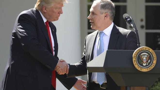 FILE - In this June 1, 2017 file photo, President Donald Trump shakes hands with EPA Administrator Scott Pruitt after speaking about the U.S. role in the Paris climate change accord in the Rose Garden of the White House in Washington. A new poll finds that less than a third of Americans support President Donald Trump's decision to withdraw from the Paris climate accord, with just 18 percent of respondents agreeing with his claim that pulling out of the international agreement to reduce carbon emissions will help the U.S. economy. (AP Photo/Andrew Harnik, File)