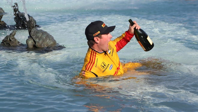 Ryan Hunter-Reay reacts to the water temperature as he enters the James Scott Memorial Fountain after winning the second race of the IndyCar Detroit Grand Prix auto racing doubleheader, Sunday, June 3, 2018, in Detroit. (AP Photo/Carlos Osorio)