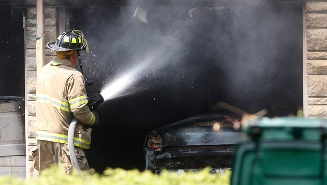 A Muncie firefighter sprays down the garage of 215 N. Forest Ave. after a fire on May 29, 2014. The body of a terminally ill man, 80, was found in the burned home.