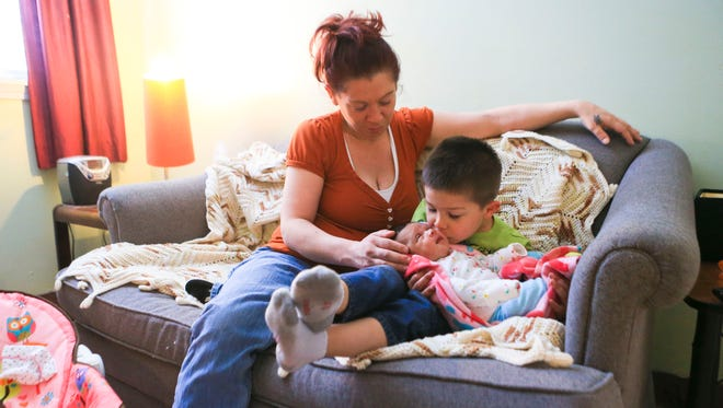 Four-year-old Miguel Diego snuggled with his newborn sister Elisabeth while mother Kymbal Pruett watched.  The trio were staying at the Freedom House in April. A former heroin addict, Pruett, 36, has been clean for several months. Pruett overdosed in 2014. Miguel witnessed her shooting heroin when he was younger.