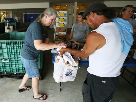 Barbara Scruggs, left, gives out food recently from