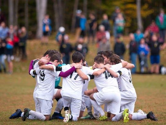 Nine Harwood players huddle on the field before Thursday's