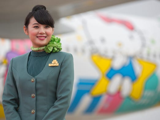 A flight attendant waits under the wing of EVA Air's