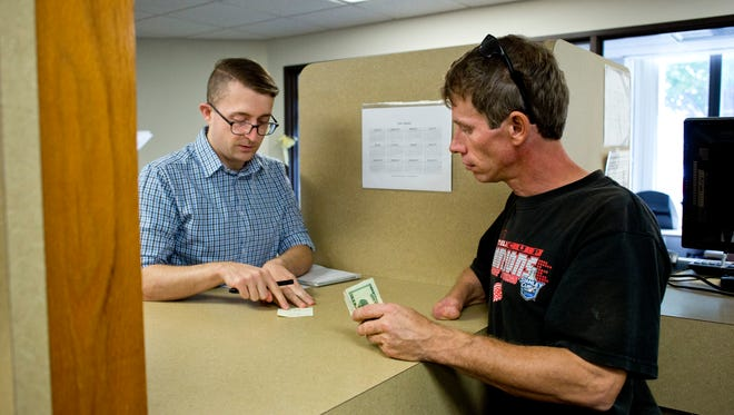 Account clerk Ryan McCann helps Fred Hedeen, of Port Huron, as he makes a child support payment Friday, October 16, 2015 at the Friend of the Court office at the St. Clair County Courthouse in Port Huron.