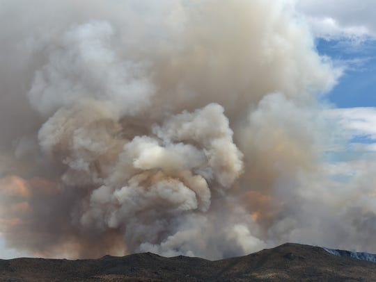 A plume of smoke raise from the Cold Springs Fire on