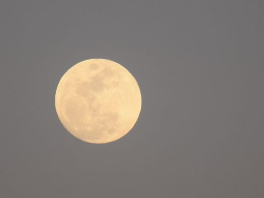 A full moon rises above the desert on Sunday, Feb.