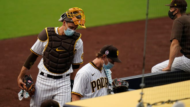 Padres starting pitcher Garrett Richards, center, walks into the dugout followed by catcher Austin Nola after the team's game against the Giants was postponed Friday night.