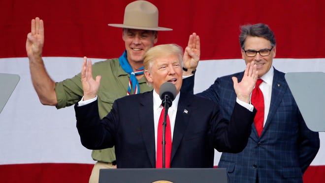 President Donald Trump gestures as former Boys Scouts, Interior Secretary Ryan Zinke, left, and Energy Secretary Rick Perry watch at the 2017 National Boy Scout Jamboree at the Summit in Glen Jean, W. Va., on Monday, July 24, 2017.