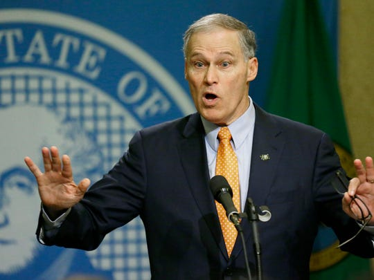 Washington Gov. Jay Inslee talks to reporters, Thursday, Feb. 23, 2017, at the Capitol in Olympia, Wash., after he signed an executive order to ensure that state workers don't help carry out President Donald Trump's immigration policies. Trump has said he wants to expand the number of deportations of people in the country illegally, and Inslee said Thursday that his order reaffirms the state's commitment to tolerance and ensures that state workers roles are to provide services for residents and not to enforce immigration statutes. (AP Photo/Ted S. Warren)