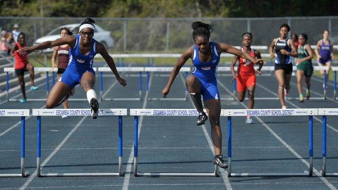Michaela Thompson, left, of Pine Forest High, competes against teammate Shaniya Sanders, right, in the 300-meter hurdles event during the FCA Panhandle Championships earlier this season. The Pine Forest girls team is seeking its eighth-consecutive district title on Wednesday at Washington High.