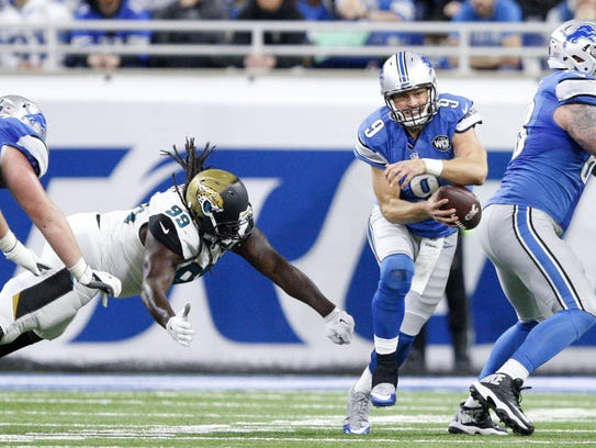 Lions quarterback Matthew Stafford (9) evades a tackle