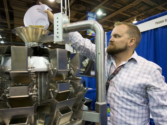 Brian Whittake, Paxiom Group's cannabis industry manager, measures cardamom pods as an example of how to use the PrimoCombi, a cannabis weigh filler, during the Southwest Cannabis Conference and Expo at the Phoenix Convention Center on Oct. 14, 2017.