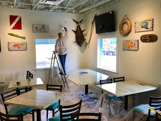 Artist Bev Feather hangs her art at Fins Seafood &