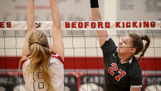 Bedford's Alyssa Griner (right) goes up for the spike against Monroe's, Chloe Maurer last season. Griner recently signed to play college volleyball at Central Michigan.