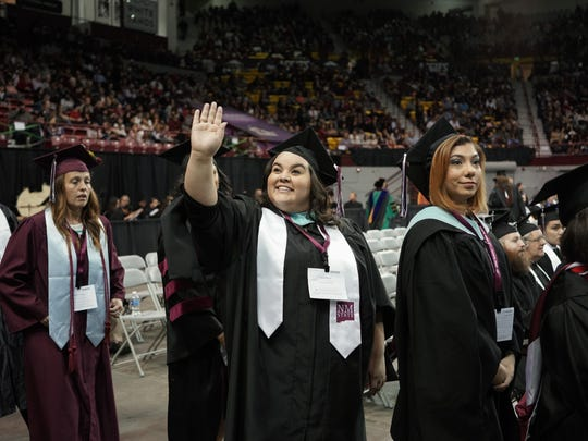 Erica Segura, graduating with a Master of Arts in Teaching, is pictured waving to people in the crowd during the NMSU commencement ceremony on Saturday morning at the Pan American Center.