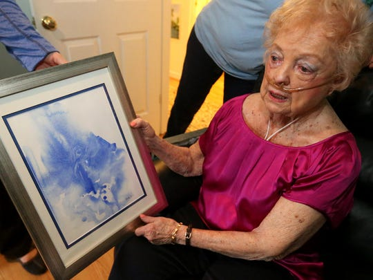 Betty Lee, an Alive Hospice patient, shows off one of her paintings of an angel that just appeared on her wet watercolor paper after she placed a brush containing blue paint to the canvas. She has been painting for more than 50 years.
