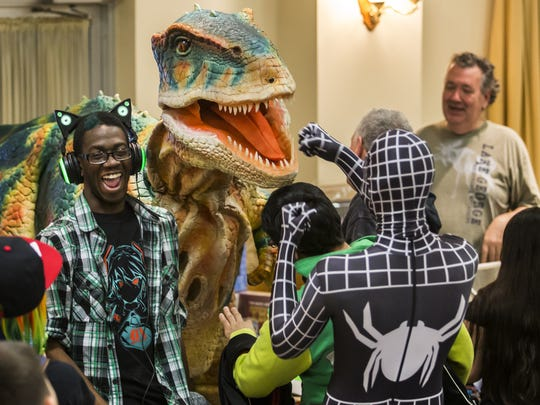 A comic book fan dressed as Spider-Man takes on a dinosaur