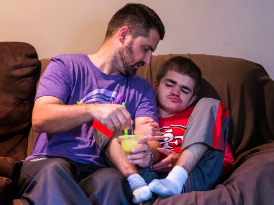 Carl Kapes feeds his eleven year-old son Ryan supplements mixed in yogurt on Saturday morning, October 29, 2016.