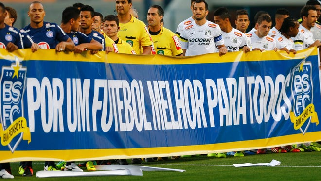 """Santos and Bahia soccer players hold a banner that reads in Portuguese; """"For a better soccer for all,"""" in protest during the Brazilian championship at the Pacaembu stadium, in Sao Paulo, Brazil on November 14, 2013."""