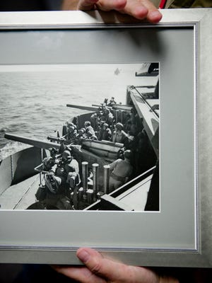 Courier-Post writer Kevin Shelly holds a photograph from WWII that depicts soldiers, including Shelly's father, on the U.S.S. Ranger off the coast of North Africa in 1942.