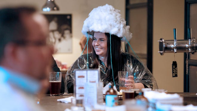 Natalie Whittington, of Heath, wore a storm cloud on her head Wednesday while celebrating the closing of the Buckeye Lake spillway at Buckeye Lake Brewery. Customers dawned raincoats and costumes hoping the lake will fill in time for boating season.