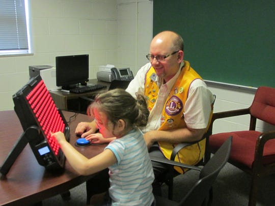 Reese Kammerer tests out the Light Aide that the Boonville Lion's Club helped get for her to use during school.