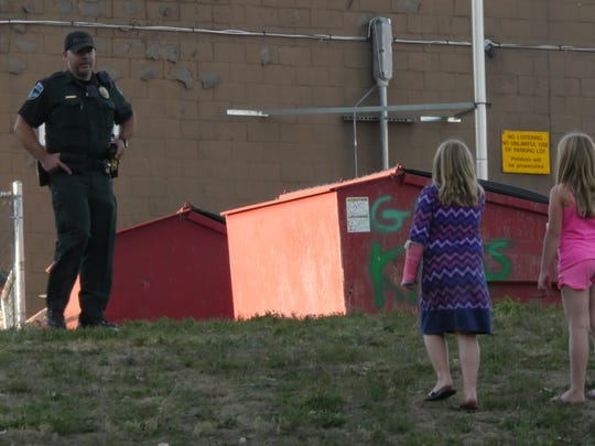 A police officer speaks to children who were playing on a playground near the O'Brien Community Center as law enforcement officers investigate an officer-involved shooting Friday evening in Winooski.