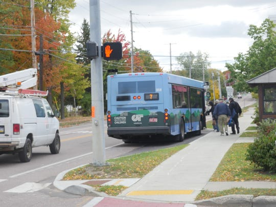 A public bus turns into an indent, installed as part of the pilot project on North Avenue, to pick up passengers.