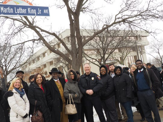 A collection of community members pose beneath a new honorary street sign on Second Street and Macy Street at an unveiling ceremony on Monday.