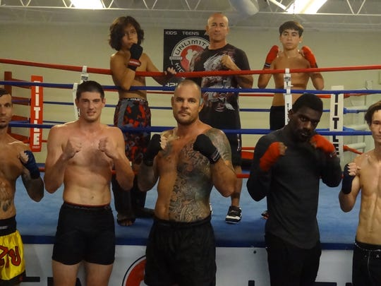 Coach David DiQuollo, back center, of Unlimited Kickboxing