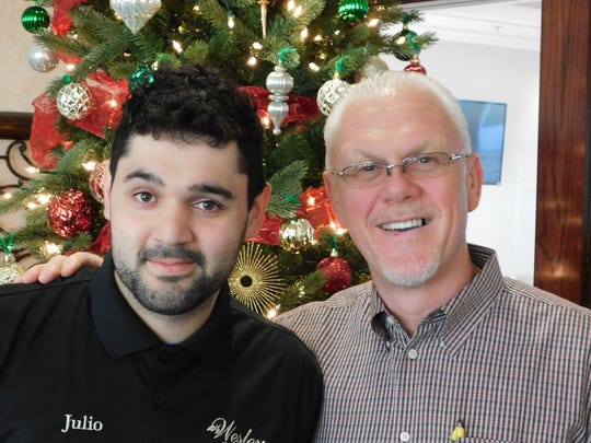 """David Allen (right), director of Dining Services at Wesley Court Senior Living, presents an achievement award to associate Julio Scaief for being the """"Overall Outstanding Employee"""" in the Dining Services Department."""