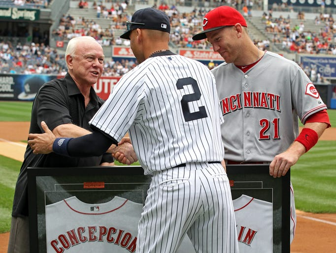 Cincinnati Reds president of baseball operations and general manager Walt Jocketty and third baseman Todd Frazier (21) present New York Yankees shortstop Derek Jeter (2) a gift at Yankee Stadium.