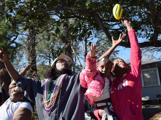 Dortany Green (left) and Keshia Johnson,  who is holding daughter Janiah Johnson, try to catch a football thrown to them at the 23rd annual krewes parade Sunday.