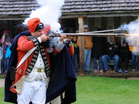 Dressed as British soldiers from the King's 8th Regiment of Foot, historical interpreters Steven Hamann, front, and Jim Evans, behind, fire musket charges at Colonial Michilimackinac.
