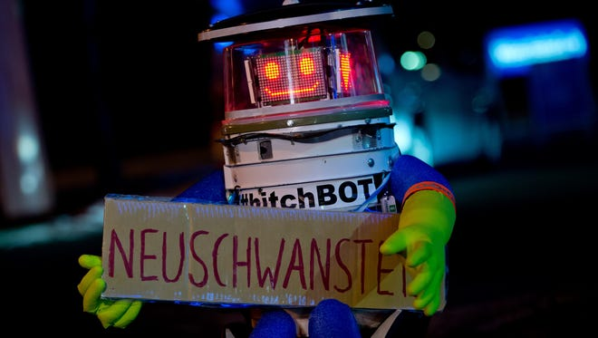 """Robot """"HitchBOT"""" is seen holding a sign reading """"Neuschwanstein"""" as he waits for a lift at the roadside in Munich, southern Germany, on February 13, 2015."""