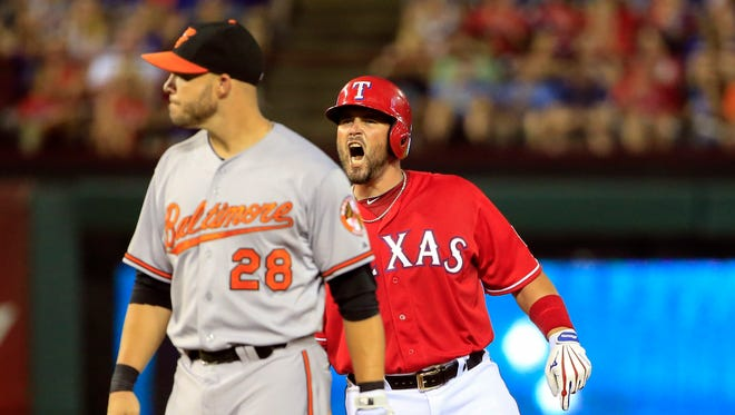 Rangers catcher Bobby Wilson reacts in front of Orioles first baseman Steve Pearce after an RBI double.