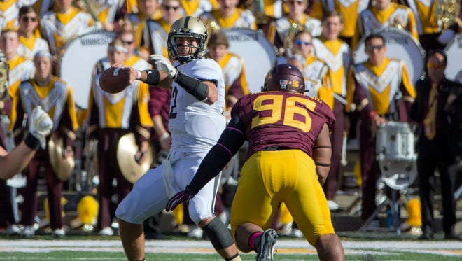 Purdue Boilermakers quarterback Austin Appleby (12) drops back for a pass as Minnesota Golden Gophers defensive tackle Steven Richardson (96) rushes in the second half at TCF Bank Stadium. The Gophers won 39-38.