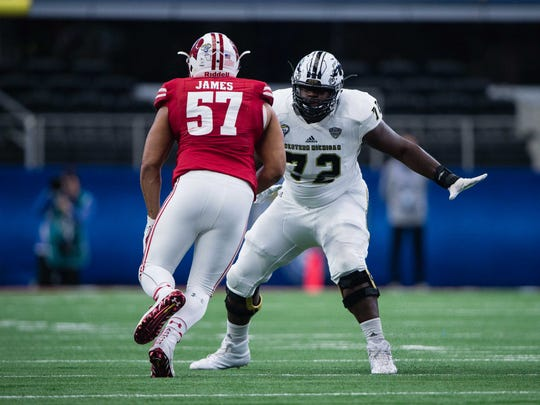 Taylor Moton, right, helped Western Michigan to an undefeated regular season, a MAC championship and a berth in the Cotton Bowl, where the Broncos lost to Wisconsin on Jan. 2. Moton is projected to be selected in the second or third round of the NFL draft.