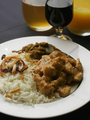 Coconut chicken with white basmati rice, fried onions, slivered almonds, eggplant and potato is among the Indian dishes being made at Gate Gourmet near O'Hare Airport as part of the Indian food that will be served on American Airlines service from Chicago to India.