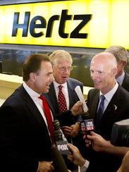Mark Frissora, left, then CEO of Hertz, and Gov. Rick